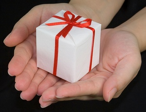 Two outstretched hands offering a small gift-wrapped box