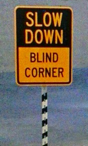 Road sign: Slow Down, Blind Corner