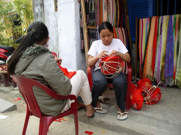 Two southeast Asian women sit in a hut constructing lanterns