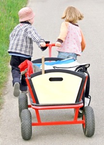 two children pull a loaded wagon together