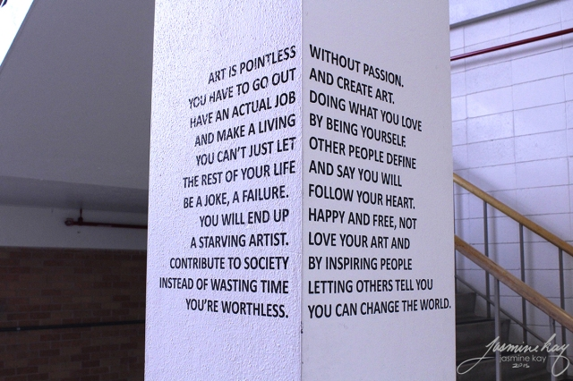 A corner view of two sides of a concrete block with text that reads like disparagement of artistic leanings from one side, but has a completely different message about embracing your true self when both sides are visible. By artist Jasmine Kay.