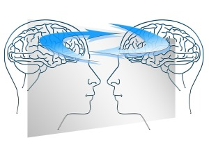 A sketch of two transparent human heads facing each other, with the brains connected by curved arrows