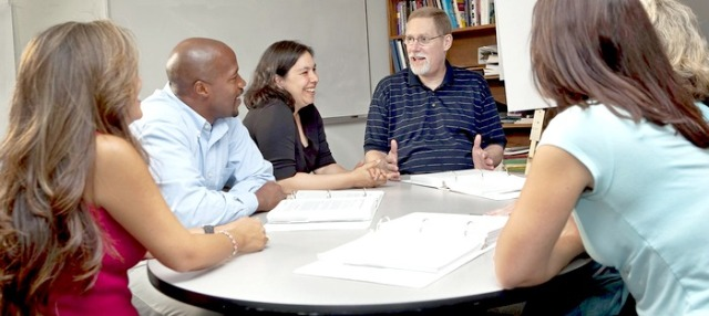 Several men and women of varied ages and races having a friendly discussion around a table in an office or classroom