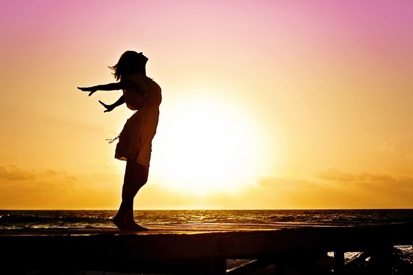 A woman stands silhouetted against a rising or setting sun, with her head throw back and arms stretched back behind her