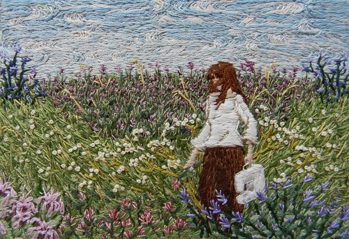 An embroidered panel of a woman in a field of flowers, carrying a sewing machine;