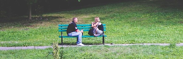 A man and a woman sit apart but facing each other and talking on a bench in a park