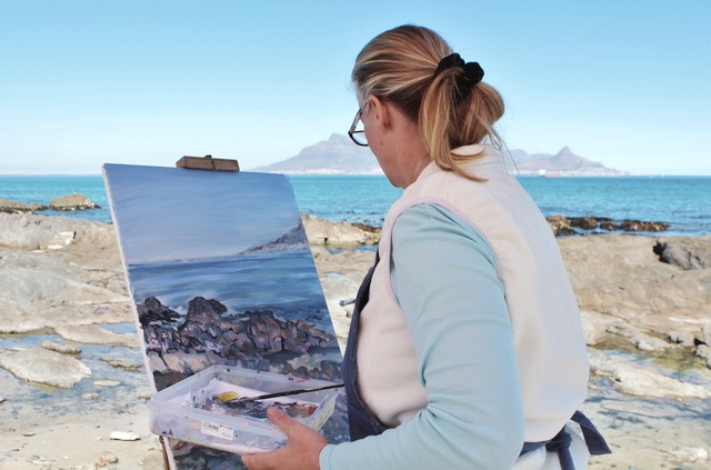 The camera looks over the shoulder of a middle-aged woman on a rocky beach painting a picture of a distant mountain
