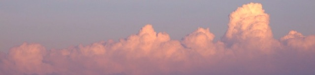 Stacked cumulus clouds tinged with pink