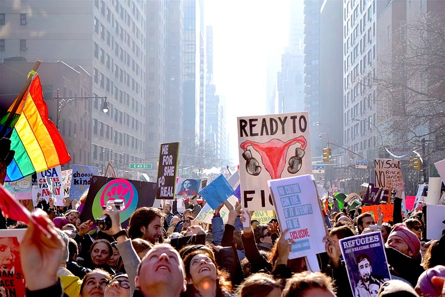 View of the January 21, 2017 women's march in a major city with protestors filling the street between tall buildings and holding signs