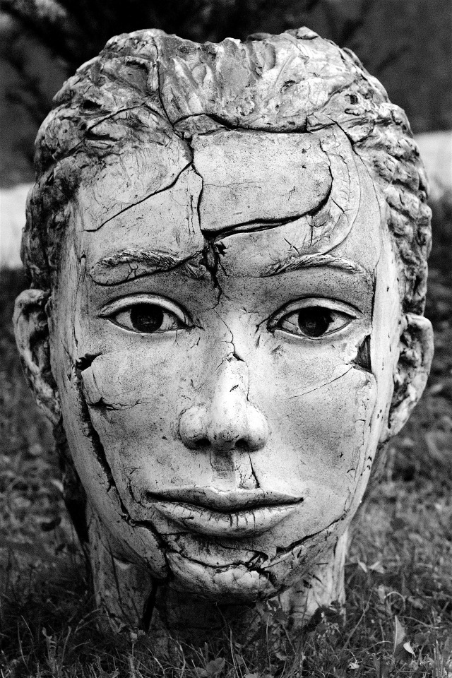 A statue of a sensitive young face. The statue has been broekn and repaired, so that there are cracks, and small pieces missing from the face.