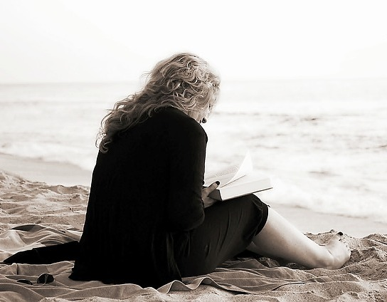 A middle-aged woman in a business suit and bare feet sits and reads a book at the beach
