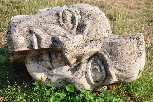The head of a statue lies on the ground. It has cracked vertically down the center of the face, and one side has slipped downward so that the two sides are skewed.