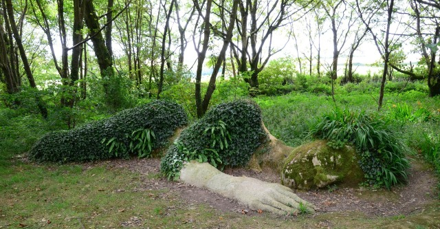 Plant-covered stone sculpture of woman sleeping stretched out on the ground as if she is halfway under the earth.