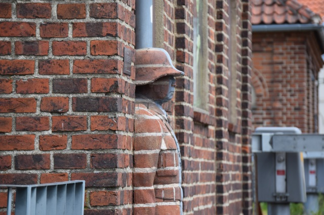 A state of a man made our of bricks is merged with a brick wall