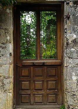 Leafy trees show through windows in a wooden door set in a stone wall.