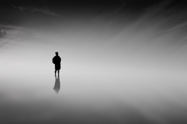 A silhouetted youth with a backpack in a completely featureless, misty space