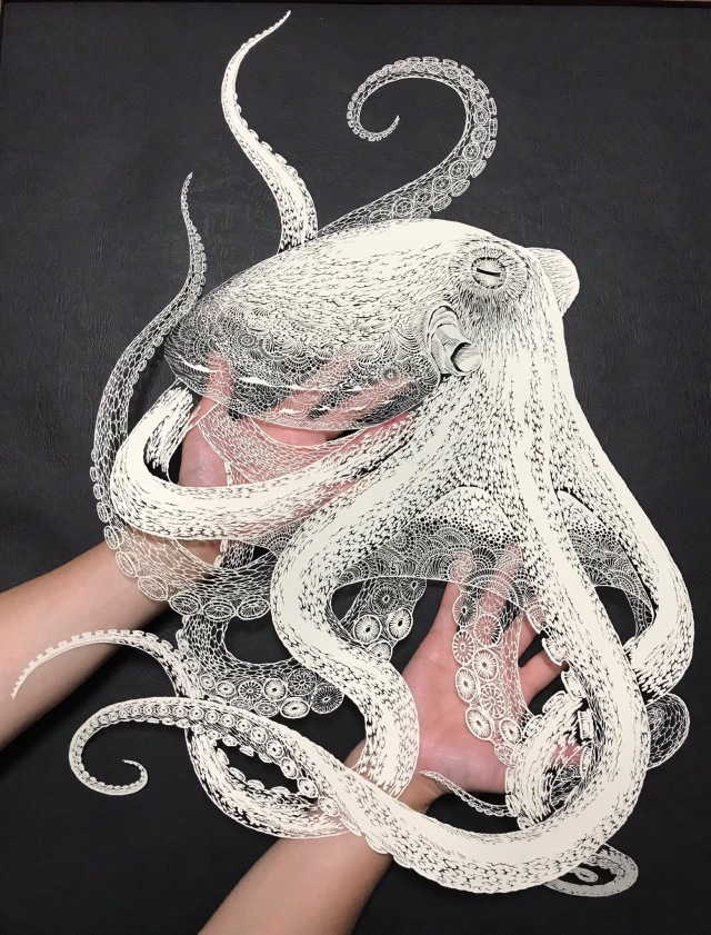 An extremely intricate octopus papercut, with thousands of teeny cutouts from a single sheet to create the impression of skin textures and overlap, laid across the artist's palms.
