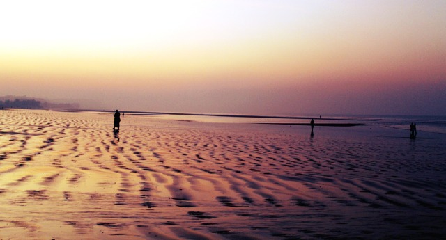 A large beach with scalloped sand patterns at dusk with a few solitary figures