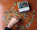 A slim hand moves jigsaw puzzle pieces laid out on a table.