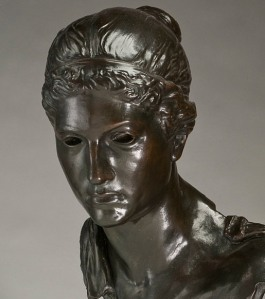 Bronze casting of a pensive young woman in ancient dress with holes for eyes