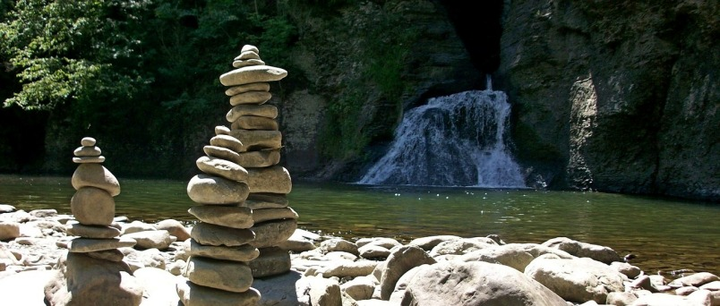 Three towers of stacked stones on a rocky river shore with a waterfall flowing down a high bank on the other side in the background